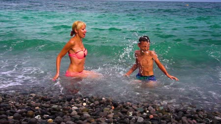 eleven people : Young slim mother and her son having fun on beach, slow motion. Family at pebble seashore in summer.