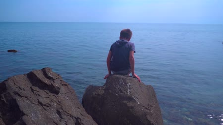 montanhismo : Boy climbing nature stones and rocks on seashore. Looking for crabs Stock Footage