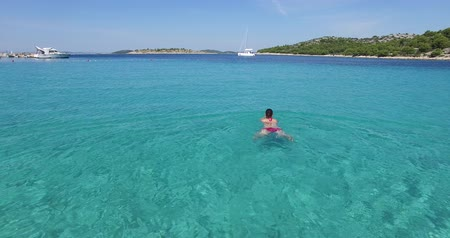высота над уровнем моря : Woman swimming in clear, clean and brilliant, shimmering turquoise sea waters, with yachts and seascape in the background. Lifestyle, travel, vacation, relax, pristine nature concept.