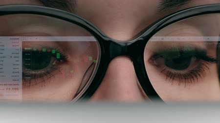 looking : Woman trader looks at screen with stock quotes candle charts. Big black glasses, eyes closeup, reflection of the display.  Source: Canon 7D, graded.