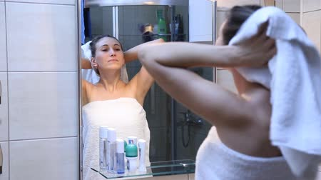 towel : she wipes the hair with a towel in front of mirror