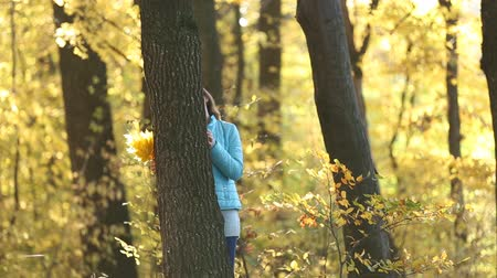 gizleme : Girl hiding behind a tree in the autumn forest