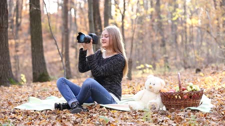kamera : Girl with a camera in the autumn forest Stock mozgókép