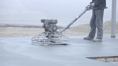 karbantartás : Worker smoothes concrete surface a special device