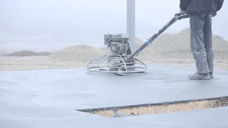 cement floor : Worker smoothes concrete surface Stock Footage
