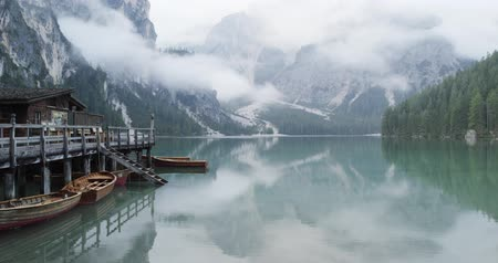 boathouse : Small boathouse with wood pier and boats on Braies lake with cloudy weather.summer adventure journey in mountain nature outdoors. Travel exploring Alps, Dolomites, Italy. 4k slow motion 60p video