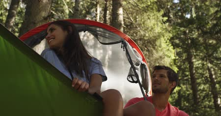 kaland : two smiling man and woman on hanging tent camping in sunny forest. Group of friends summer adventure journey in mountain nature outdoors.People travel exploring Alps, Italy. 4k slow motion 60p video Stock mozgókép