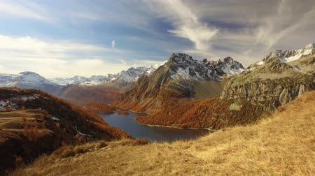 fall through : POV walking on fall discovering woods, valley lake and snowy mounts.Sunny autumn day Hiking in colorful red forest wild nature mountain outdoors.Alps Devero.4k point of view establishing video