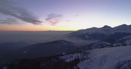 kurmak : Backward aerial top view over winter snowy mountain and woods forest at sunset or sunrise.Blue hour dusk or dawn twilight Alps mountains snow season establisher.4k drone flight establishing shot Stok Video