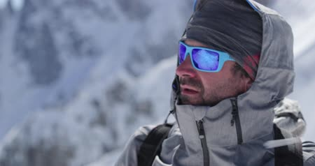 portre : Climber mountaineer man portrait on snowy mount top in sunny day.Mountaineering ski activity. Skier people winter snow sport in alpine mountain outdoor.Side view.Slow motion 60p 4k video