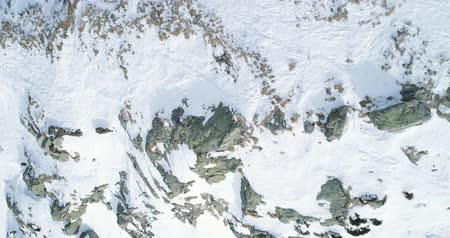 kurmak : Overhead aerial top view over winter snowy mountain rocks.Rocky mountains covered in snow and ice glacier.Winter wild nature scape outdoor establisher.4k drone flight straight-down establishing shot