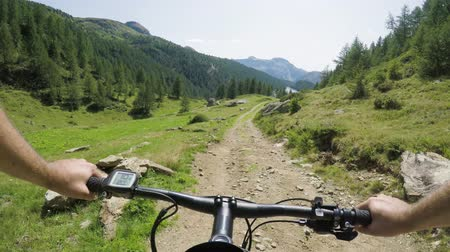 POV man riding e-bike on downhill near lake.Mtb action cyclist exploring trail path near mountains.Electrical bike active people sport travel vacation in Europe Italy Alps outdoors in summer.4k video