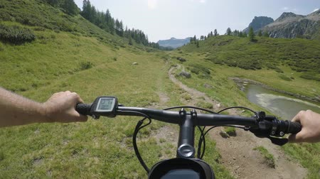mtb : POV man riding e-bike on hill near lake.Mtb action cyclist exploring trail path near mountains.Electrical bike active people sport travel vacation in Europe Italy Alps outdoors in summer.4k video