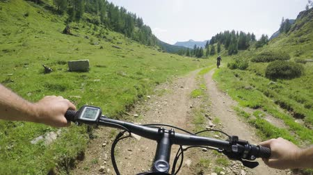 POV man riding e-bike following friend woman.Mtb action cyclist exploring together mountain trail path.Electrical bike active people sport travel vacation in Italy Alps outdoors in summer.4k video