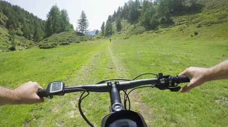 mtb : POV man riding e-bike following friend woman.Mtb action cyclist exploring together mountain trail path.Electrical bike active people sport travel vacation in Italy Alps outdoors in summer.4k video