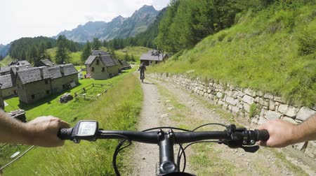 obec : POV man riding e-bike to town village.Mtb action cyclist exploring path near mountains.Electrical bike active people sport travel vacation in Europe Italy Alps outdoors in summer.4k video