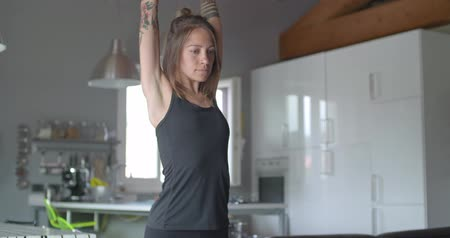 young tattooed woman warming up doing stretching before fitness sport workout at home .Living room domestic training. 4k slow motion video