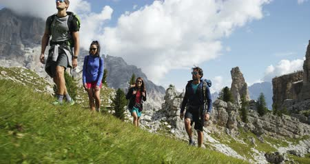 dolomitok : Four friends walking along wild hiking trail path. Group of friends people summer adventure journey in mountain nature outdoors. Travel exploring Alps, Dolomites, Italy. 4k slow motion 60p video Stock mozgókép
