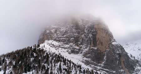 назад : Backward aerial with snowy mountain and woods forest at Sella pass.Cloudy bad overcast foggy weather.Winter Dolomites Italian Alps mountains outdoor nature establisher.4k drone flight