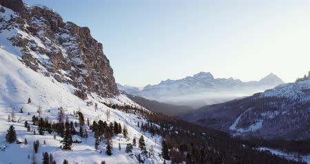 toward : Forward aerial to snowy valley with woods forest at falzarego pass.Sunset or sunrise, clear sky.Winter Dolomites Italian Alps mountains outdoor nature establisher.4k drone flight Stock Footage