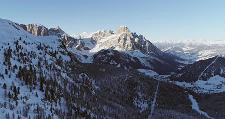 назад : Backward aerial to snowy alpine valley with woods forest at Piz Boe.Sunny sunset or sunrise,clear sky.Winter Dolomites Italian Alps mountains outdoor nature establisher.4k drone flight