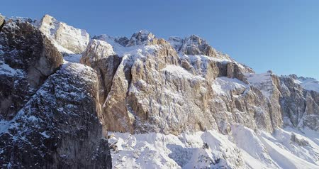 назад : Backward aerial along snowy alpine steep rocky cliff valley.Sunny day,clear sky.Winter Dolomites Italian Alps mountains outdoor nature establisher.4k drone flight