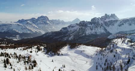 toward : Backward aerial to snowy alpine valley with woods forest at Cinque Torri.Sunny sunset or sunrise,sunny day,cloudy sky.Winter Dolomites Italian Alps mountains outdoor nature establisher.4k drone flight Stock Footage