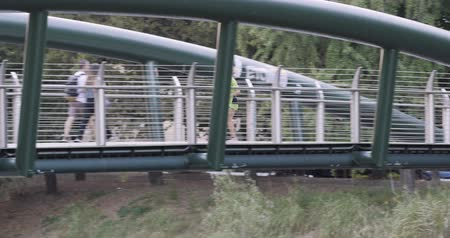 merdiven : Young blond woman in fitness wear running training on modern bridge.Side panning long shot.Summer sunny day.Industrial green city.Urban runner cardio healthy activity workout.4k slow motion 60p video Stok Video