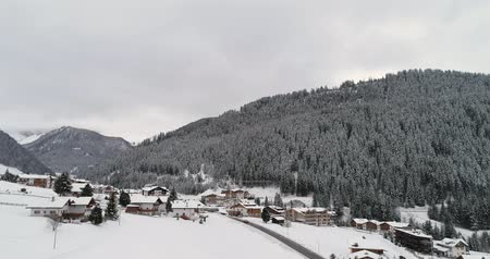dolomitos : Aerial near town overed in snow.Cloudy bad overcast foggy weather.Winter Dolomites Italian Alps mountains outdoor nature establisher.4k drone flight establishing shot