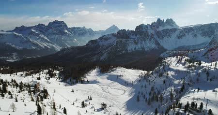 toward : Forward aerial to snowy alpine valley with woods forest at Cinque Torri.Sunny sunset or sunrise,sunny day,cloudy sky.Winter Dolomites Italian Alps mountains outdoor nature establisher.4k drone flight