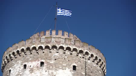 makedonia : White tower in Thessaloniki with waving Greek flag, Greece Stock Footage