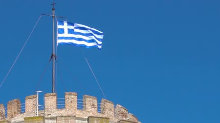 zár : Waving greek flag on the top of the White Tower in Thessaloniki, Greece
