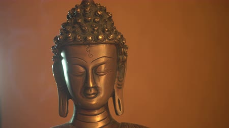 buddhista : Copper statuette of Buddha,  Buddhas face close-up and smoke of incense sticks Stock mozgókép