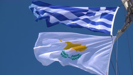 greek flag : Waving Greek and Cyprian flags agaist the blue sky in strong wind Stock Footage