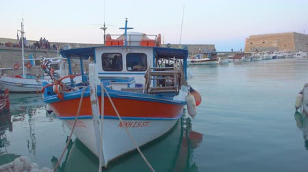 mooring : HERAKLION, GREECE - APRIL 26, 2018: Fishing boat near Venetian Fortress in old port of Heraklion in the evening, Crete, Greece Stock Footage