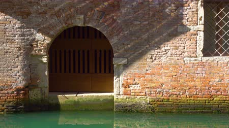 main : Small gate of old house by canal in Venice and moving sun reflections on the wall, Italy Stock Footage