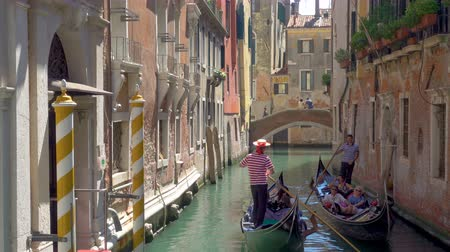 two rows : Venice, Italy - June 18, 2018: Brief encounter of two gondoliers at narrow canal in Venice Stock Footage