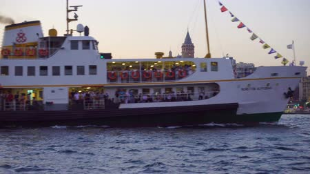 pleasure boats : Istanbul, Turkey - July 15, 2018: Tourist pleasure ship goes near the Galata Bridge in Istanbul in the evening