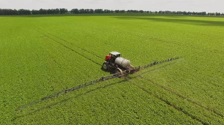 weeding : Tractor spraying pesticides on soybean field with sprayer at spring. Aerial Quadcopter Shooting