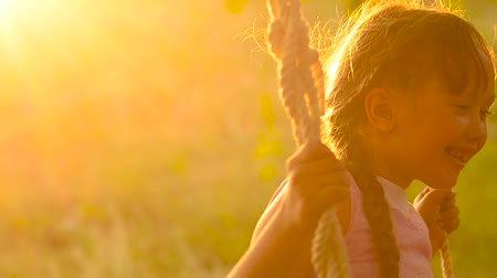 The girl shakes on a swing on a sunset