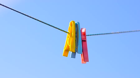 varal : colored clothes pegs on linen rope, swing on background of blue sky.