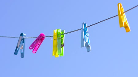 varal : colored clothespins on clothesline, swinging wind against blue sky. Vídeos