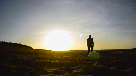 ing : silhouette of man with ball standing on the beach lit by sun. Stock mozgókép