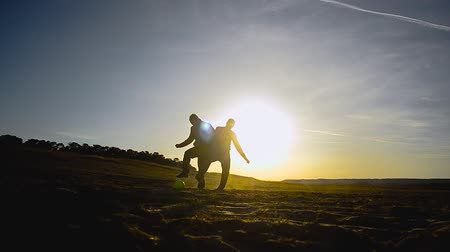 ing : silhouettes of men playing football on beach in spring of, two guys playing football on sand in the sun. Stock mozgókép