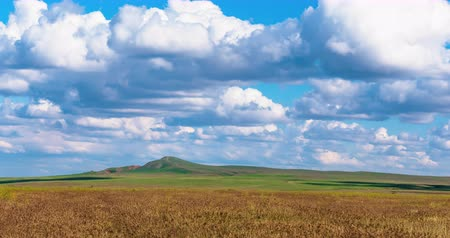 astrakhan : Timelapse beautiful landscape clouds over the green field 4K FULL HD Clouds float in the sky. Movement of white clouds in the blue sky. Mount Bogdo National Park.