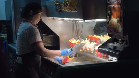 mcdonalds : Moscow, Russia - September 16, 2017: Woman frying potato in McDonalds