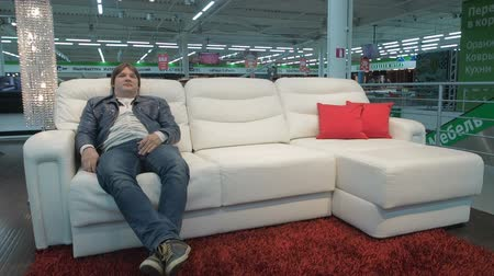 automatický : MOSCOW, RUSSIA - SEPTEMBER 13, 2017: Happy man testing automatically folding sofa in a market. Man choosing new smart sofa-transformer in furniture store Dostupné videozáznamy