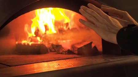 open hearth : Man warms his hands by the fire. Furnace fire. Video clip of burning firewood in the fireplace. Firewood burn in the oven. 30fps Full HD. Stock Footage