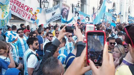 kutluyor : MOSCOW, RUSSIA, JUNE 20, 2018: Soccer World Cup Argentine football fans with flags at the on Nikolskaya Street, a crowd with mobile phones in their hands Stok Video