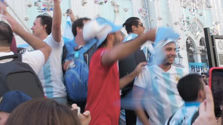 támogató : MOSCOW, RUSSIA, JUNE 20, 2018: Soccer World Cup Argentine football fans in caps with symbols of the national team with flags at the on Nikolskaya Street jumping singing songs, a crowd with mobile phones in their hands